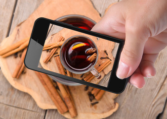 Hands taking photo mulled wine with smartphone