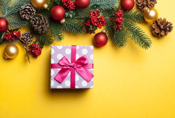 gift box and pine branches on yellow background.