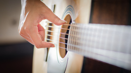 woman's hands playing acoustic guitar