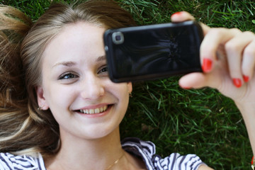 smiling girl taking a self portrait with smart phone.