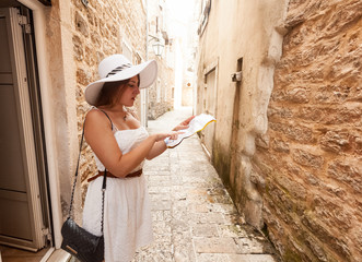 elegant woman in white hat looking at paper map on old narrow st