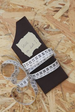 """A measuring band around bar of chocolate.""""Still on diet"""""""