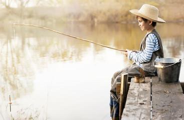 Printed kitchen splashbacks Fishing Boy fishes on a bridge on the lake