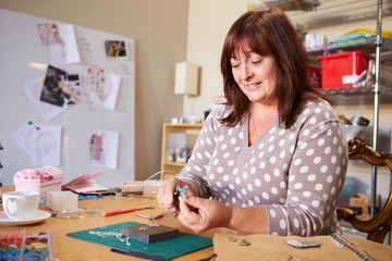 Mature Woman Making Jewelry At Home