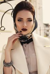 beautiful elegant girl in beige coat and silk scarf