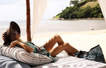 sexy woman in swimsuit and hat relaxing on beach of Phuket