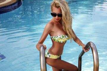 sexy woman  in bikini and sunglasses posing in swimming pool
