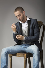 Elegant young man in  sitting on a stool while buttoning his sle