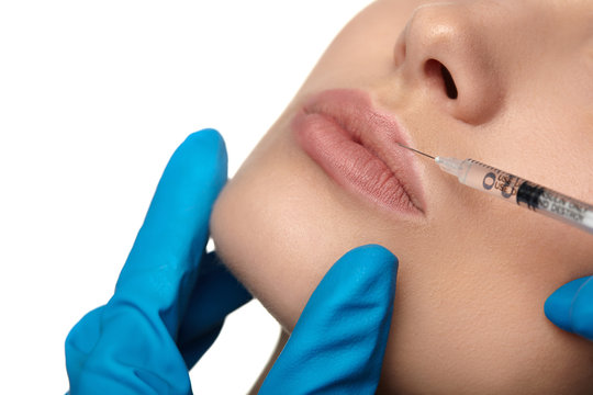 Woman receiving cosmetic injection in lip