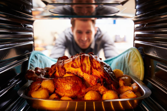 Man Taking Roast Turkey Out Of The Oven