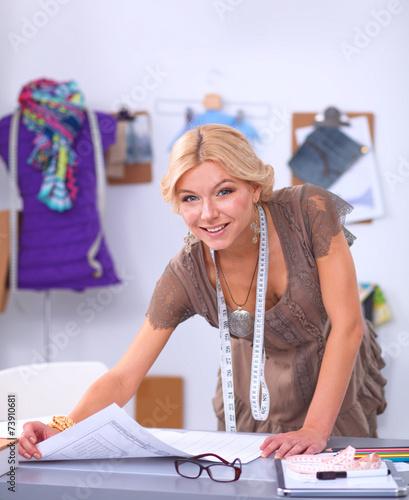 modern young fashion designer working at studio. Black Bedroom Furniture Sets. Home Design Ideas