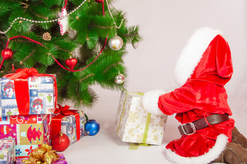 Baby in Santa costume at the Christmas tree with gifts