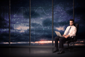 Businessman holding laptop in office room with graph charts on w