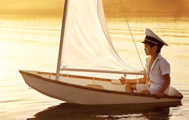 Boy floats on a boat with a sail