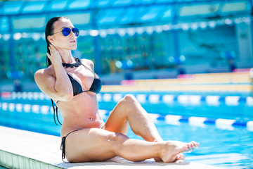Young pretty fashion sport woman posing  in  pool