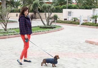 Women walking around town with dachshund dog