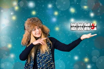 Winter girl presenting new year 2015 calendar.