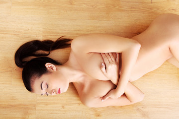 Above view of naked woman lying on the floor