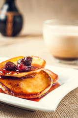 pancakes with jam and coffee on burlap background