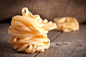 Homemade tagliatelle. Uncooked pasta on the wooden table