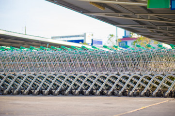 Row of shopping cart with green handles on parking near supermar