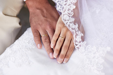 Couple holding hands against wedding dress
