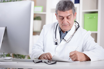 physician with stethoscope around his neck working in office