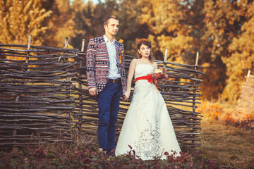 Bride and groom standing near the wicker fence holding hands