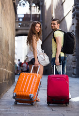 young pair with luggage walking through city