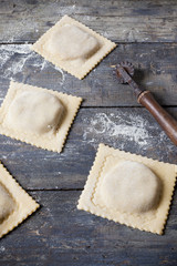 homemade fresh stuffed ravioli big size on wooden table