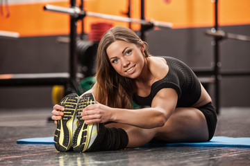 beautiful girl in the gym, doing warm-up before exercise