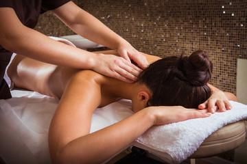 Masseur doing massage on woman body in the spa salon.