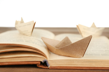 Origami boats on old book on wooden table, on white background