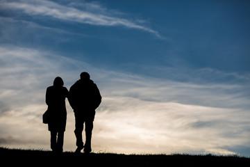 silhouette of elderly couple in sky