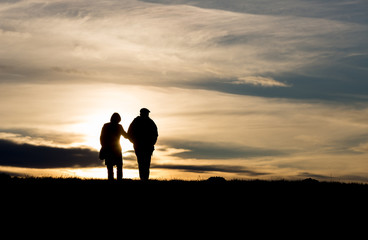 silhouette of elderly couple walking on hill