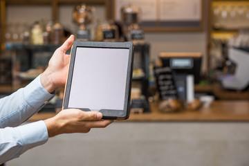Hand hält Tablet / Hoch / vor Café Kulisse mit Platz für Text