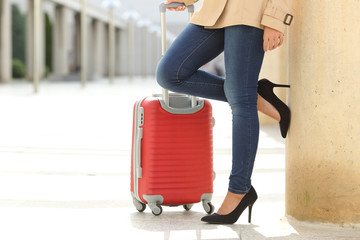 Tourist woman legs waiting with a suit case in an airport