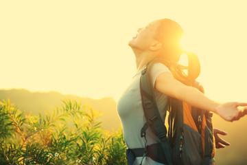 woman hiker open arms at sunrise mountain peak