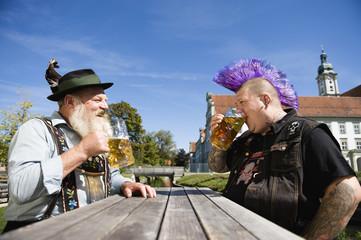 Deutschland, Bayern, Oberbayern, Mann mit Irokesenschnitt und Mann in bayerischer Tracht im Biergarten