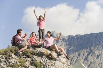 Italien, Südtirol, Familie sitzen auf Fels, Mann Foto machen