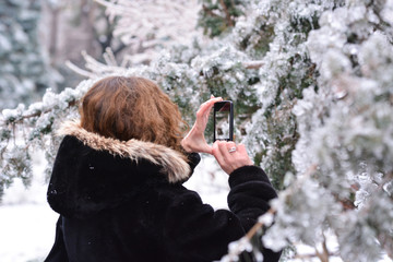Women taking photo with the phone to the ice on trees