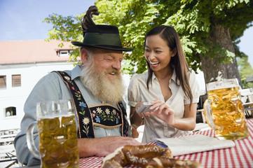 Deutschland, Bayern, Oberbayern, Asiatische Frau und Mann im bayerischen Biergarten, Lachen