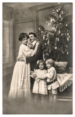 victorian family parents and children with christmas tree
