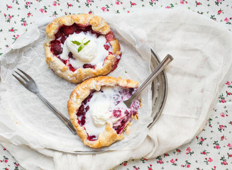 Small rustic berry galettes with ice-cream on a silver dish