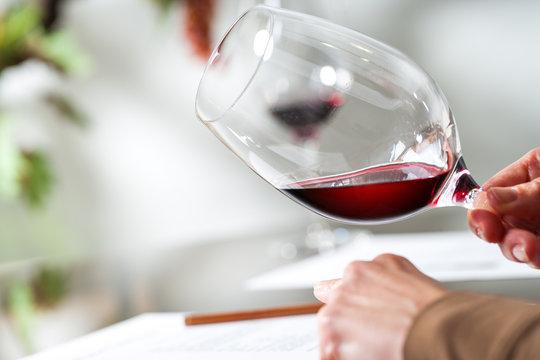 Sommelier evaluating wine at tasting.