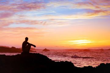 woman sitting alone at sunset near the sea
