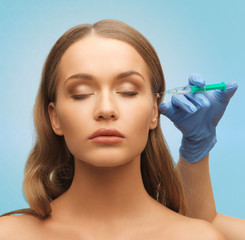beautiful woman face and hand with syringe
