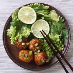 Fish balls in curry sauce with fresh herbs close up. top view