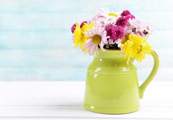Beautiful flowers in pitcher on table on light blue background