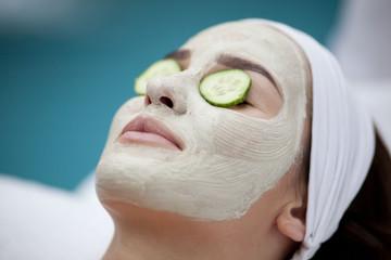 Beautiful young woman receiving facial mask of cucumber in beaut